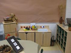 Transforming a classroom inspired by Reggio. Basket of pinecones an a natural colored table cloth on the table.