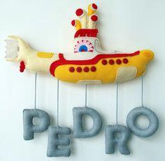 Enfeite para porta maternidade tema Submarino Amarelo. <br>Pode ser usado para decorar o quarto do bebê posteriormente. <br> <br>Possui aproximadamente 30cm de largura. <br>Valor para nomes com máximo de seis letras. <br>Acima de seis letras, acréscimo de R$10,00 por letra adicional (o tamanho do enfeite também será ajustado). <br> <br>Desenvolvemos em quaisquer temas e/ou modelos à sua escolha.