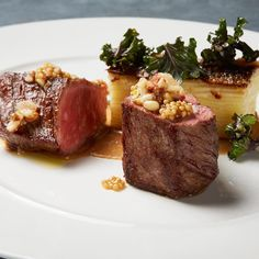 """New York strip steak -- grilled to a perfect medium rare, topped with pink peppercorns and toasted pine nuts. Plated with a """"bar"""" of cheesy potato grain (garnished with toasted kale leaves.)"""