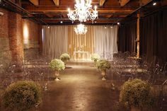 Industrial indoor ceremony space softened with drapery, baby's breath and chandeliers down the aisle!