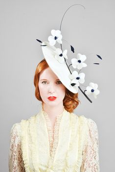 Gallia This is a really elegant and sophisticated headpiece.  An ivory silk  saucer adorned with a handsewn orchid with ivory silk petals, navy satin buds and navy stripped coque feathers.