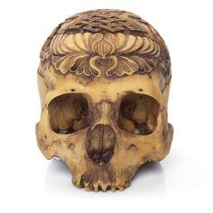 This remarkable new item is a detail-rich cast resin skull embellished with intricately carved detail. Cast from a real human skull carved with a tantric Asian lotus motif and finished with a realistic aged patina, this eye-catching piece will look great staring back from your mantelpiece or curio shelf.  This nifty new skull has been a consistently strong seller since we started carrying it!