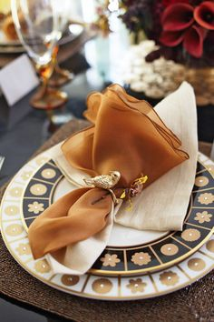 Toasty colors dress this table set for an autumn luncheon. Black-trimmed plates contrast with white-trimmed chargers, both embellished with gold. - Photo: Colleen Duffley