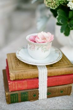 Fresh flowers in an antique tea cup atop a bundle of old books. This creates an interesting centerpiece at any angle