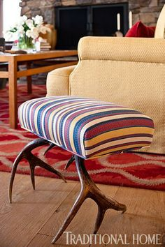 A stool with antler legs is covered in a striped fabric from Robert Kime. - Traditional Home ®/ Photo: Michael Garland / Design: Trip Haenisch