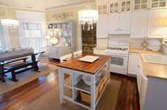 Charming Cream Walls and Antique Plates viaThistlewood. Tall cabinet with glass doors on top. Calming colors. Warm floors mirrored in the island