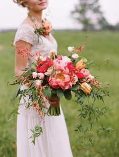 Bride with floral necklace and stunning bouquet in a palette of pink, blush and rust orange including garden roses, tulips, orchids and peonies. Florals by Southern Blooms by Pat's Floral Designs, bride's dress by Sarah Janks, image by Jen Fariello.