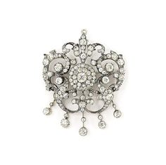 A late 19th century diamond brooch Of cartouche design, the old-cut diamond cluster centre to the similarly-set scrolling foliate openwork surround, suspending a diamond-set fringe with knife-bar connections, circa 1890, 7.0cm long, later rhodium plated, replacement detachable brooch fitting and folding pendant loop