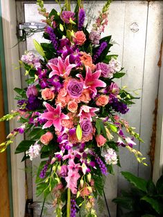 Funeral Standing Spray with pinks and violets  focal flowers being pink roses and stargazer lilies.