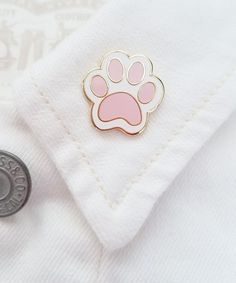 "This cutie patootie pink paw print is the perfect pin for the pet lover. - Size: 0.875"" wide - Cloisonné Hard Enamel Pin - 18 kt Gold Plated - Rubber Clutch Clasp Shipping Details In-stock items will"