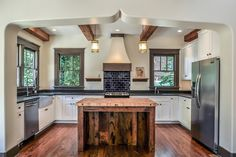 eclectic kitchen.dark trim, tile, and counters. rustic island. hood.