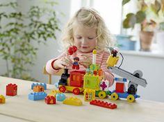 Mädchen spielt mit LEGO DUPLO MickeyMinnie Geburtstagsparade Löschfahrzeug und Lastwagen