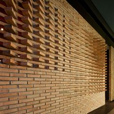 Dude Cigar Bar by Studiomake  --  Twisted bricks create openings in the walls of a speakeasy-style bar in Bangkok, allowing passers-by a sneaky glimpse inside.