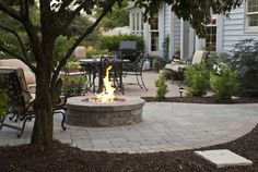 Outdoor fireplace with mulch, planted trees and patio.