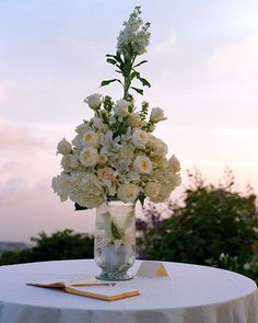 White flowers decorate an outdoor guest book table