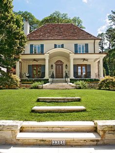 A remodeled 1920s Colonial receives a country French makeover. A barrel roof crowns the home's new porch, French blue shutters pop against the pale yellow exterior, and the mahogany front door receives the royal treatment when it is capped with a Napoleon-hat detail.