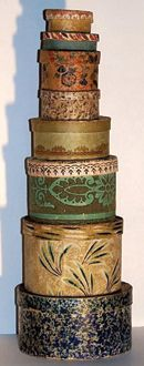 """A graduated stack of eight early wallpapered bandboxes, with diameters ranging in size from 2.5"""" to 6"""". Diminutive bandboxes sometimes were referred to as 'minikins.'"""