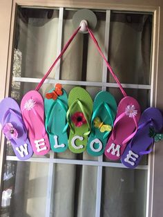 """Flip Flop Welcome sign.  Directions:  I bought 4 sets of sm flip flops from the dollar store. Glued them together with a hot glue gun. I also used some small plastic tubing I had hanging around to """"anchor"""" it. You could use a small piece of would as well. I had wooden letters so I painted them white, you could simply write welcome on the flip flops or use card board paper. Glued the letters to the bottom. I then glued, again, glue gun, to the second flip flop in on each side for the ribbon…"""
