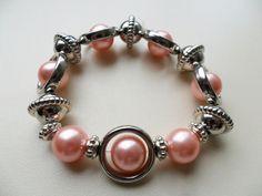 pulsera elasticada en perlas rosadas pasantes en sama diseño de color beads.