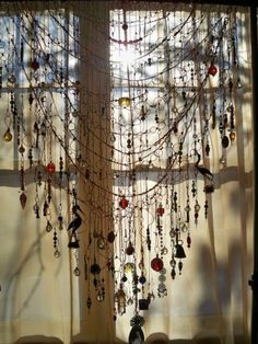 curtain of found objects. Ooh soo many broken jewellery and childrens creations.