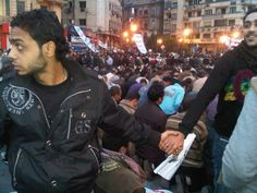 Christians protect Muslims during prayer in the midst of the 2011 uprising in Cairo, Egypt.