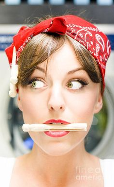 Humor Face Shot Of A Woman Looking To The Side With A Shocked And Surprised Expression When Holding Wooden Clothes Peg In Her Mouth In Crazy About House Work by Ryan Jorgensen