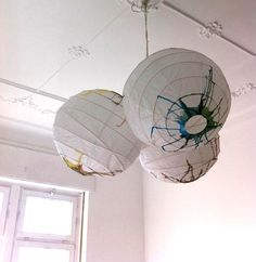 """Maigaard bought a trio of """"anonymous, cheap"""" Regolit Pendant Lamp Shades from Ikea ($4.99 each) and created a hanging lamp """"made much more interesting with watercolor paint."""""""