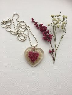 HURRY! BIGGEST SALE OF THE SEASON  For 20% USE COUPON CODE:  BIGGESTSALE2  (MINIMUM PURCHASE £6)  Delicate and Elegant Handmade Item * Materials: Real, Dried Dark Pink Heather and Babysbreath Flowers in Resin. This Beautiful Real Flower Heart Pendant has been attached to a Small Silver Heart Bail and a delicate Silver Snake Chain a Silver Plated Necklace,which is nickel and lead free.  * Size: The Heart pendant is 1.26 inches wide (3.2cm) Chain length 18 inches (45cm) With 1mm wide Chain…