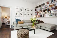 Platsbyggd bokhylla ovanför soffan