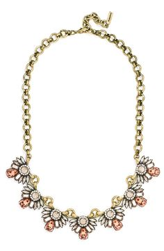 A dusting of pastel-pink crystals adds ladylike color to this floral-inspired collar necklace crafted with antiqued goldtone links for a vintage feel.
