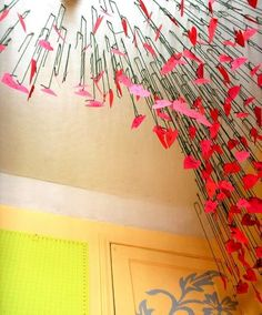 Posted on February 02, 2012 12:02PM by Angela Swinderman Elias    Hang tons of red and pink paper hearts at different lengths to create this sculptural overhead design.