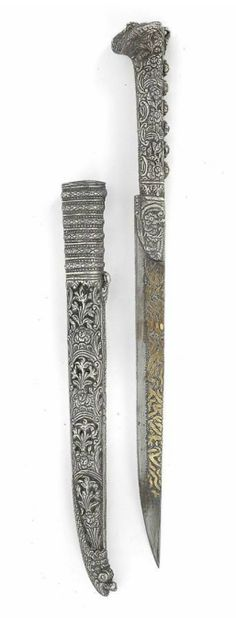 Turkey: An ornamental 'Bicak' knife,  Turkish-Ottoman. The long narrow single-edged iron blade engraved with ornamental brass inscription. Handle and scabbard with elaborate floral décor and moulded volutes, made of silver and with parcel-silver parts. The scabbard terminates in the head of a mythical animal. 19th Cent.