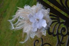 Cream and white lace bridal flower with feathers. via Etsy.