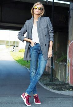 A white t-shirt is paired with a gray blazer, skinny jeans, Puma sneakers, and mirrored sunglasses