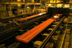 "Glowing slabs of hot steel roll down the caster at #2 Steel Producing at the ArcelorMittal Cleveland site, photographed on Thursday, September 28, 2016. The slab at right has just been cut by torches into the desired length. All slabs are 9"" deep, but may vary by width and length. (Thomas Ondrey/The Plain Dealer)"
