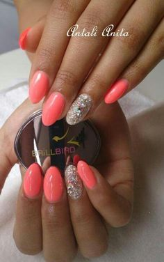 Almond shape nails, coral pink nail polish with sparkly rhinestone ring finger