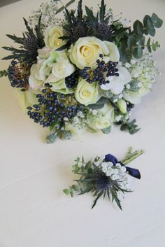 Bridal Bouquet and boutineer with winter white Avalanche Roses, Blue Eryngium Thistles, Classic Hydrangeas, Midnight Blue Viburnum Berries, Eucalyptus Globus and white Freesia and Gypsophilia, Diamante detail and a very snazzy semi naked handle completes the design