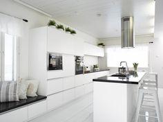 Moderni valkoinen ja selkeälinjainen keittiö. Vetimien tilalla vetolaatikoiden yläosassa on huomaamattomat sormiurat. #puuvaja