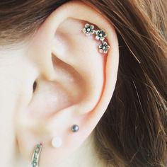 Chica con un piercing en la oreja en forma de flores