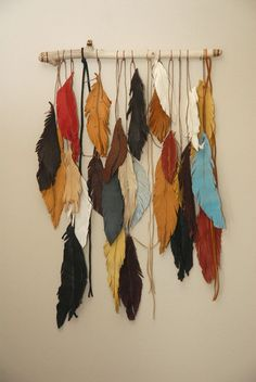 This listing is for a tribal boho wall hanging. With all of the leather feather making I do, why would I not make a wall hanging with them? Several color so leather feather hung on a burned wooden piece of driftwood. Tribal designs are on the ends of the wood and the feather have some simple designs on them too. This is about 13 wide and 20 long. There are a couple of pieces of fringe added in too and if you happen to hang this were it gets an occasional waft of air it will move with the…