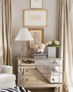 Elegant bedroom features stacked abstract nude sketches placed over a mirrored dresser topped with a crystal baluster lamp and a Nate Berkus Ikat Bowl flanked by windows dressed in champagne colored silk curtains.