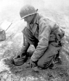 Battle of the Bulge. A US soldier placing mines on a road to try a slow the German spearhead.