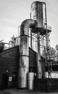 Black and white photograph of Sloss Furnaces National Historic Landmark in Birmingham Alabama factory, industry, storage tank, fuel and power generation, water tank, architecture, low angle view, built structure, silo, industrial building, smoke stack, no people, sky, cooling tower, electricity, tank, water conservation, day, water tower - storage tank, outdoors, agricultural building, oil refinery, petrochemical plant
