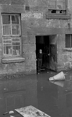 A young boy looks out at flood water in front of his home...