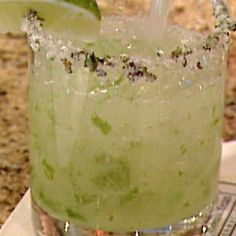 Frozen Royal Mojito sugar (rim) 4 mint leaves (minced plus sprigs for garnish) 4 pieces lime rind (removed) 1 1/4 ozs rum (bacardi limon) 3/4 oz mojito mix syrup (online) 1 cup ice (cubes) 1 lime (cut into wedges for garnish)