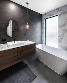Squared off white free standing bathtub, dark timber vanity with white marble top, squared off white basin, matte black tap and mixer, pear shaped mirror. Grey Marble Bathroom, Charcoal Bathroom, Modern Bathroom Tile, Bathroom Interior Design, Bathroom Flooring, Small Bathroom, Bathroom Ideas, Dark Floor Bathroom, Dark Brown Bathroom