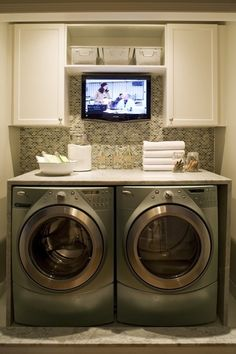 now THIS is how you do a laundry room! tabletop for folding, simple cabinets to hide stuff, and a tv for watching while folding! @ House Remodel Ideas - Fox Home Design Laundry Room Storage, Laundry Room Design, Laundry In Bathroom, Laundry Rooms, Laundry Area, Laundry Closet, Basement Laundry, Laundry Tips, Laundry Station