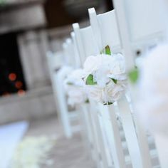 White roses tied to the white chairs that line the wedding aisle | One Fine Day Photography | villasiena.cc