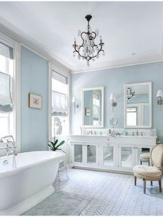 A white bathroom with pale blue walls, a mirrored vanity, and a herringbone tile floor pattern. Source: http://www.zillow.com/digs/Home-Stratosphere-boards/Luxury-Bathrooms/