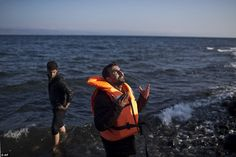 A man prays after disembarking from a boat transported from the nearby Turkish coast at a beach on the northern shore of Lesbos